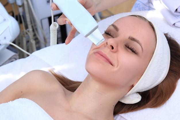 Kobieta poddawana terapii oczyszczającej profesjonalnym aparatem ultradźwiękowym w gabinecie kosmetologicznym