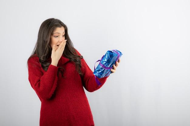 Kobieta podekscytowana świątecznym pudełkiem z fioletową wstążką.
