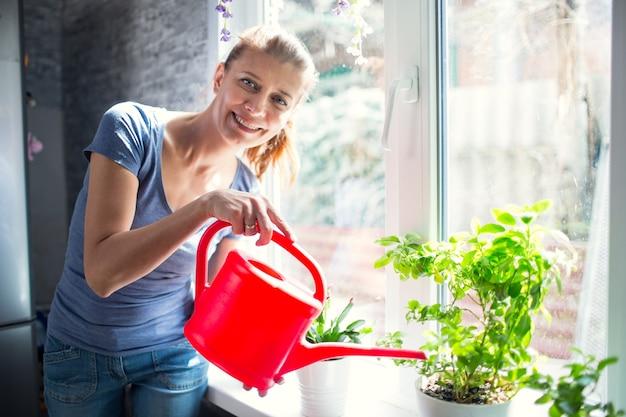 Kobieta podlewa kwiaty w domu na oknie