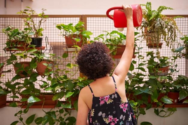 Kobieta podlewa rośliny na podwórku swojego domu