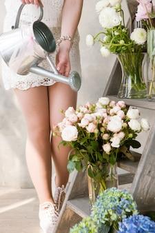Kobieta podlewania bukietów świeżych kwiatów świeżych kwiatów. smukła kwiaciarnia pracuje w kwiaciarni ze świeżymi bukietami. piękny wystrój na wesele