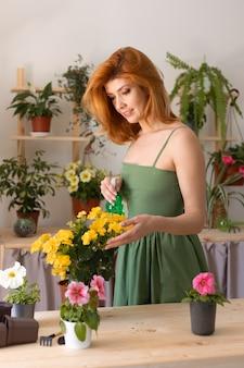 Kobieta podlewania kwiatów średni strzał
