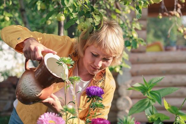 Kobieta podlewania kwiatów w ogrodzie. kobieta w średnim wieku zajmująca się ogrodnictwem. ona jest szczęśliwa.
