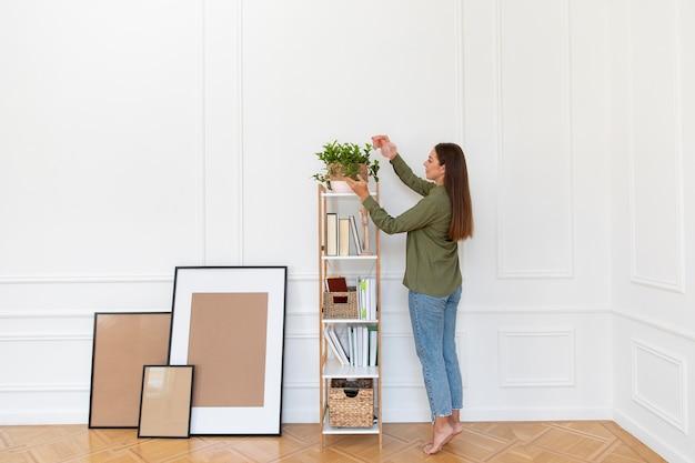 Kobieta podlewania roślin pełny strzał