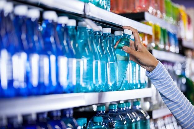 Kobieta podnosi butelkę woda