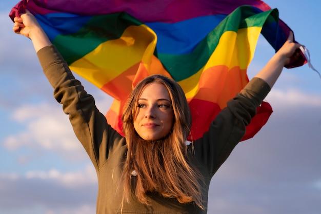 Kobieta podnosi flagę dumy gejowskiej