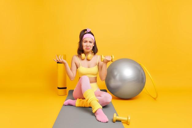 Kobieta podnosi hantle siada na macie fitness ubrana w strój sportowy dos aerobik w domu ma niezadowolony wyraz twarzy