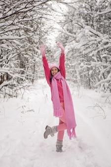 Kobieta podnosi ręce do góry stojąc na ścieżce w lesie w różowym ubraniu kurtka, szalik z dzianiny i czapka stoi zimą w zaśnieżonym lesie