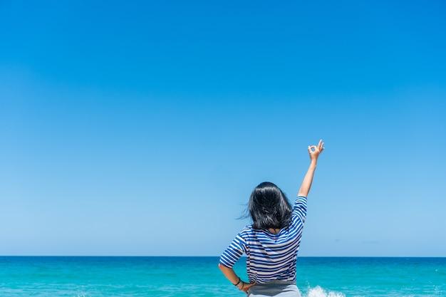 Kobieta podnosi ręce do nieba koncepcja wolności z błękitnym niebem.