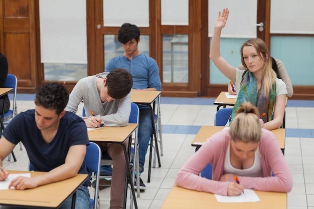 Kobieta podnosząc rękę podczas egzaminu