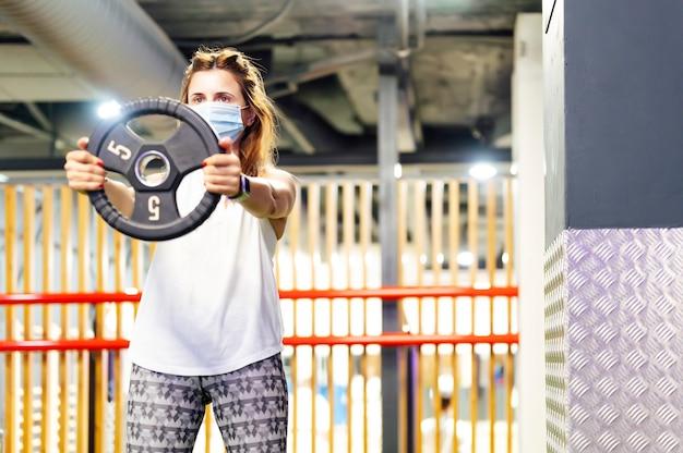 Kobieta podnosząca ciężary na siłowni z maską