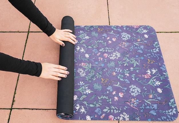 Kobieta podnosząca matę po wykonaniu sesji jogi. fioletowa mata w kwiaty