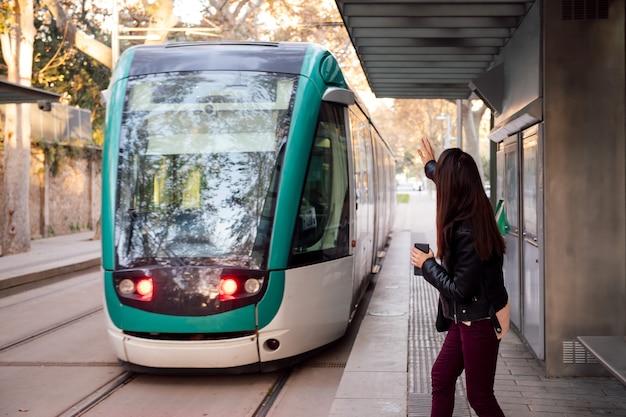 Kobieta podnosząca rękę, żeby wezwać tramwaj