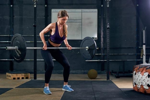 Kobieta podnoszenia brzana w siłowni