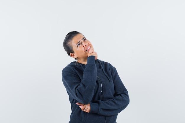 Kobieta podpiera brodę na dłoni w bluzie z kapturem i wygląda zamyślona. przedni widok.