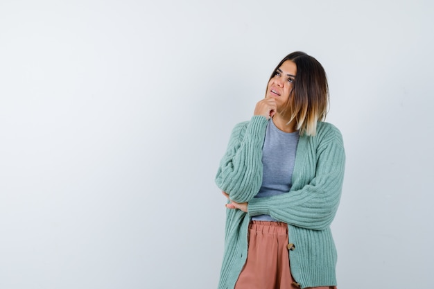 Kobieta, podpierając brodę pod ręką w ubranie i patrząc zamyślony, widok z przodu.