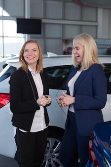 Kobieta podpisująca polisę ubezpieczenia samochodu, agent wskazuje na dokument