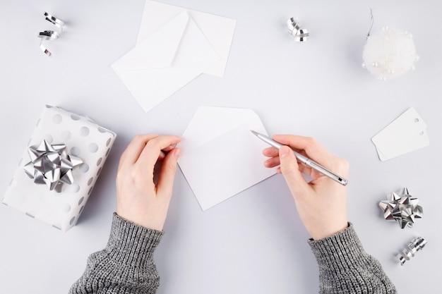 Kobieta podpisuje białą kopertę na prezent w srebrnym opakowaniu. koncepcja przygotowania do wakacji