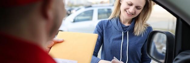 Kobieta podpisuje dokumenty i odbiera żółtą kopertę pocztową. koncepcja dostawy ekspresowej