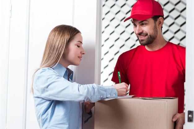 Kobieta podpisuje dostawę z kurier chłopiec w czerwień mundurze