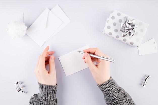 Kobieta podpisuje kartę na prezent w srebrnym opakowaniu, szare tło. koncepcja przygotowania do wakacji