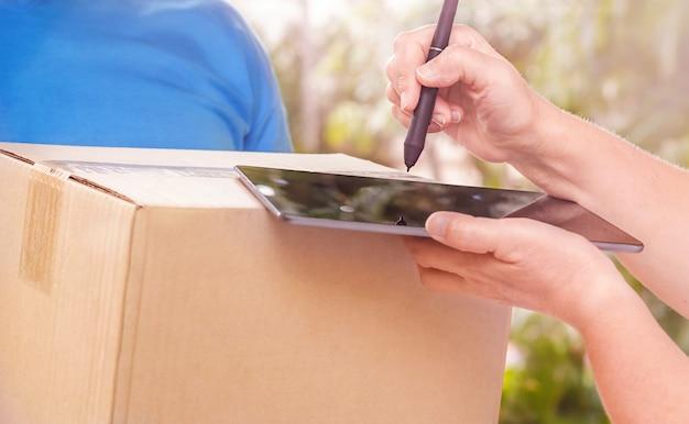 Kobieta podpisuje na tablecie doręczenie przesyłki