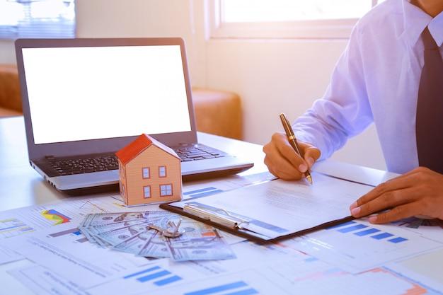 Kobieta podpisuje umowę na zakup domu z agentem nieruchomości.