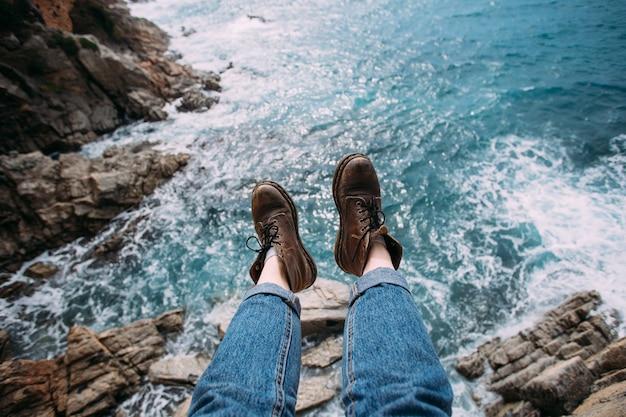 Kobieta podróżniczka w niebieskich dżinsach i grubych brązowych skórzanych butach na wycieczki piesze siedzi na skraju klifu