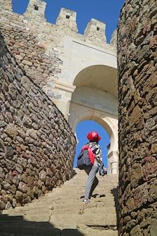 Kobieta podróżniczka wspinająca się po schodach kompleksu twierdzy rabati, miasto achalciche, gruzja
