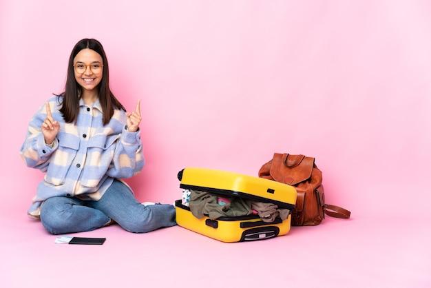 Kobieta podróżniczka z walizką na podłodze, wskazująca na świetny pomysł