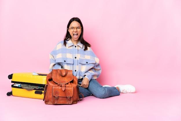 Kobieta podróżniczka z walizką siedząca na podłodze i krzycząca do przodu z szeroko otwartymi ustami