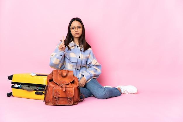 Kobieta podróżniczka z walizką siedząca na podłodze, licząc jedną z poważnym wyrazem twarzy