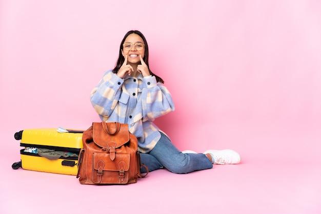 Kobieta podróżniczka z walizką siedząca na podłodze uśmiechnięta z radosnym i miłym wyrazem twarzy
