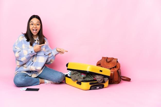 Kobieta podróżniczka z walizką siedząca na podłodze zaskoczona i wskazująca na bok