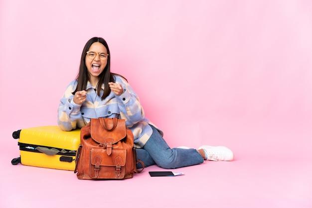 Kobieta podróżniczka z walizką siedząca na podłodze, zaskoczona i wskazująca na przód