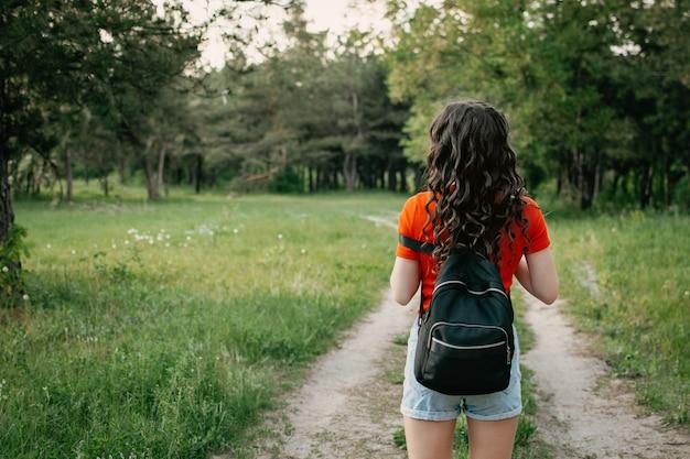 Kobieta podróżnik młoda dziewczyna turysta spaceru na wiejskiej drodze.