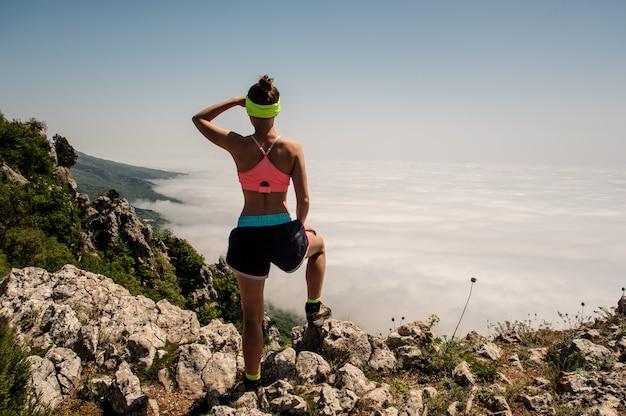 Kobieta podróżnik na górskim szczycie nad chmurami podróżuje styl życia