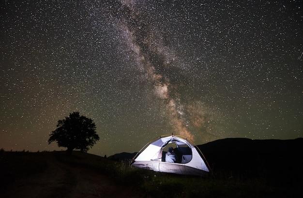 Kobieta podróżnik odpoczywa przy noc campingiem w górach. widok z tyłu dziewczyny wycieczkowicza siedzi w oświetlonym namiocie, podziwiając widok niesamowitego pięknego gwiaździstego nieba i drogi mlecznej