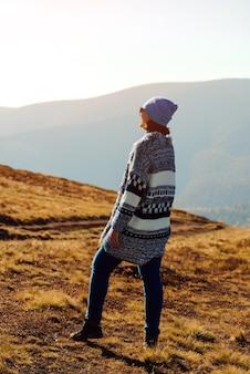 Kobieta podróżnik patrząc na wschód słońca nad jesiennymi górami.