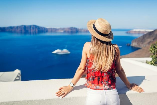 Kobieta podróżnik patrzeje kalderę od fira lub thera, santorini wyspa, grecja. turystyka, podróże, wakacje koncepcja