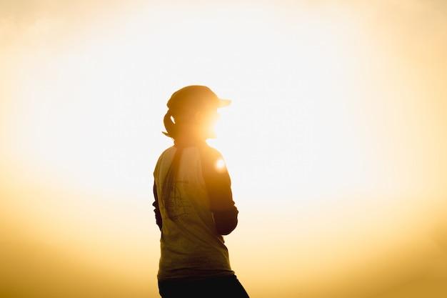 Kobieta podróżnik przy zmierzchem lub wschód słońca pozycją dosięgał góra wierzchołka szczytu cel podczas hiki