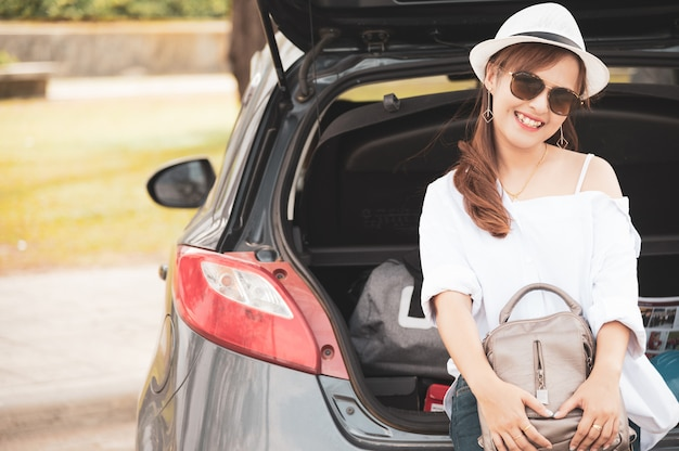 Kobieta podróżnik siedzi na samochodzie hatchback