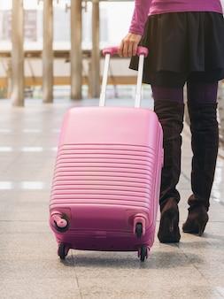 Kobieta podróżnik spaceru w lotnisko chodnik z torba podróżna.