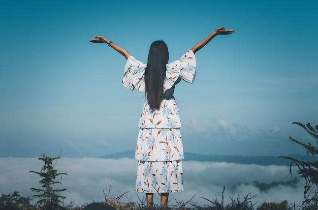 Kobieta podróżnik stojąca z uniesionymi rękami patrząc mglisty w górach o wschodzie słońca.