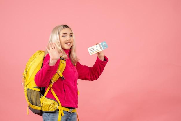 Kobieta podróżnik widok z przodu z plecakiem macha ręką trzymając bilet