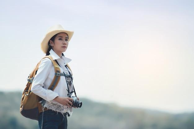 Kobieta podróżnik wycieczkuje z plecakiem przy góra krajobrazem