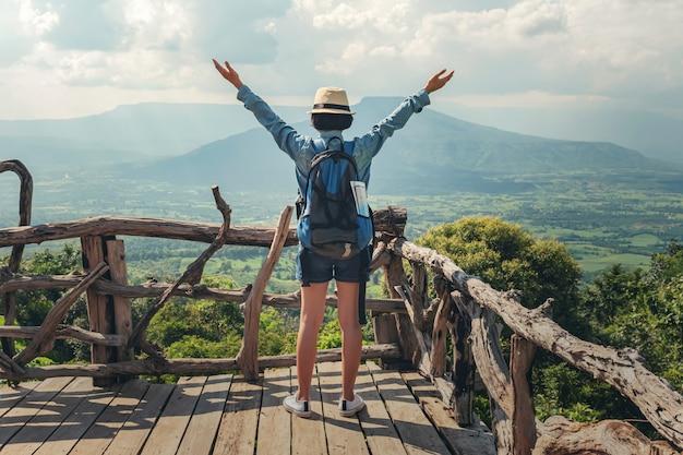 Kobieta podróżnik z plecakiem cieszy się widok i szczęśliwą wolność przy górami