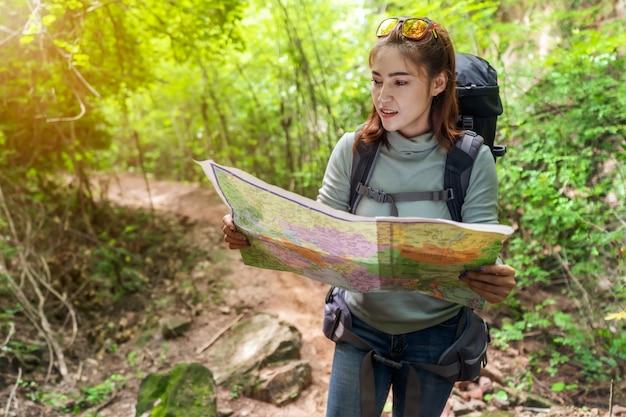 Kobieta podróżnik z plecakiem i mapy wyszukiwania kierunkach w lesie