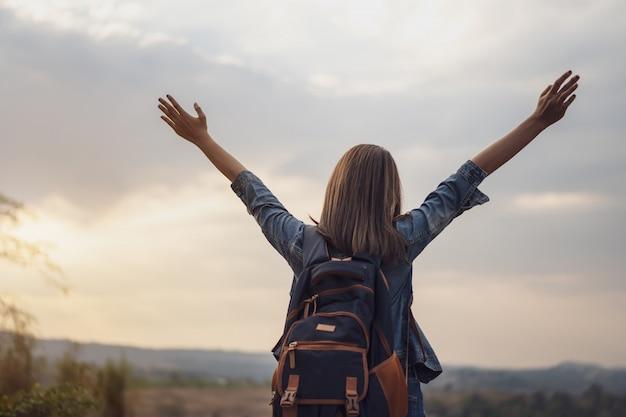 Kobieta podróżnik z plecakiem z podniesionymi rękami