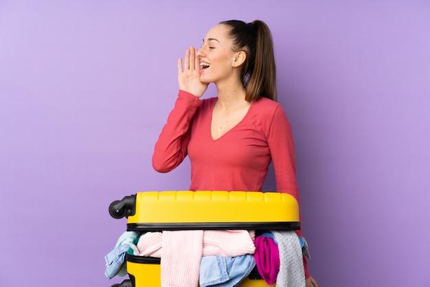 Kobieta podróżnik z walizką pełną ubrań na pojedyncze fioletowe ściany krzyczy z szeroko otwartymi ustami